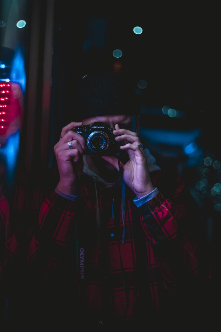 Mann mit Kamera in der Nacht vor Leuchtreklame