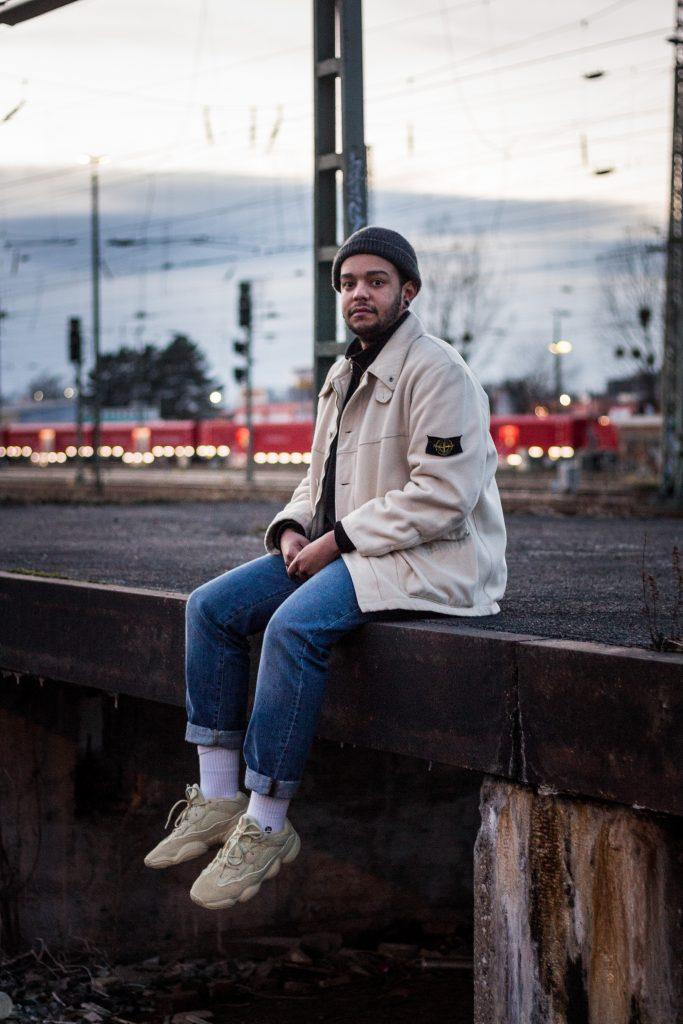 sitzende Person in der Abenddämmerung am Bahnhof mit Stone Island Jacke und Yeezys